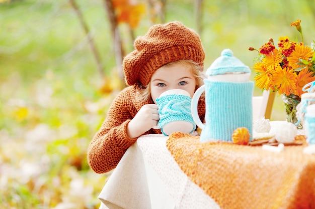 Adorable niña bebiendo té en el parque otoño