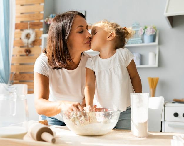 Adorable niña besa a su madre