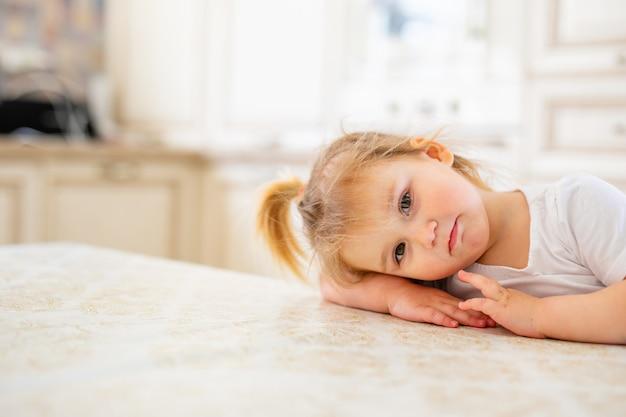 Adorable niña en blanco dormitorio soleado. niño recién nacido relajante en una cama azul. guardería para niños pequeños.