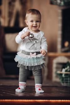 Adorable niña con bola de navidad plateada