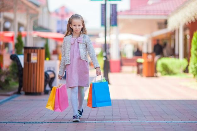 Adorable niña con bolsas de compras caminando en la ciudad al aire libre