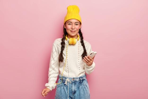 Adorable niña de cabello oscuro con coletas, usa un teléfono móvil para navegar por las redes sociales, usa un elegante sombrero