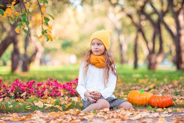 Adorable niña con calabaza al aire libre en un cálido día de otoño.
