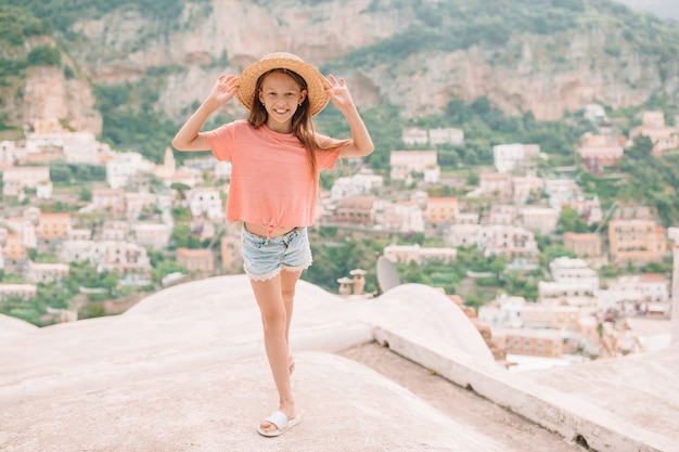 Adorable niña en un cálido y soleado día de verano en la ciudad de positano en italia