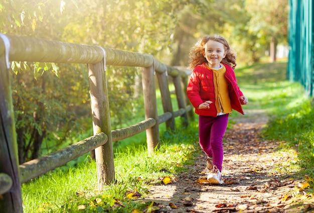 Adorable niña caminando en el parque en un día de otoño.