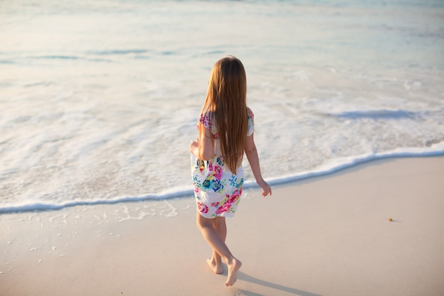 Adorable niña caminando en la playa tropical blanca