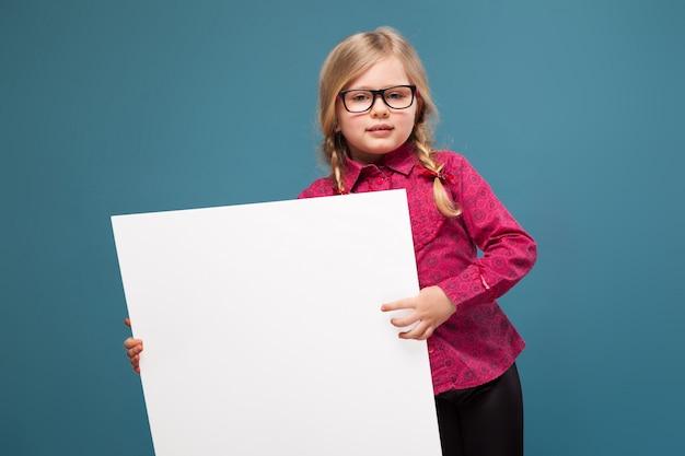 Adorable niña en camisa rosa, pantalón negro y gafas tiene cartel en blanco vacío