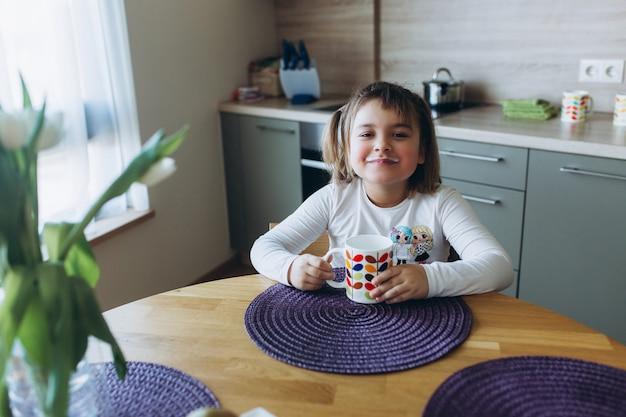 Adorable niña caucásica desayunando en casa en la acogedora cocina en estilo de diseño escandinavo.