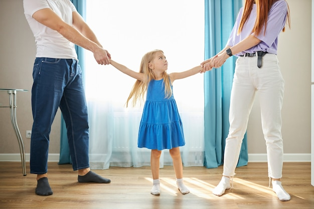 Adorable niña caucásica entre padres deprimidos