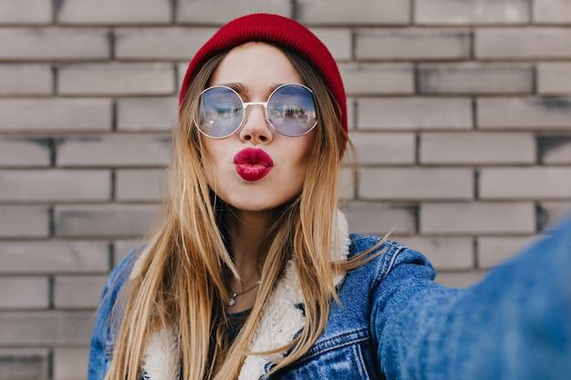 Adorable niña caucásica con peinado recto posando con expresión de la cara de besos en la pared de ladrillo. tiro al aire libre de la dichosa dama blanca con gafas y sombrero rojo expresando amor mientras hace selfie.