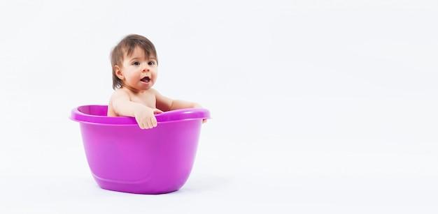 Adorable niña caucásica tomando baño en tina púrpura sobre fondo blanco.