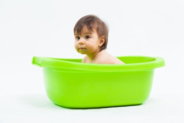 Adorable niña caucásica tomando baño en tina verde sobre blanco