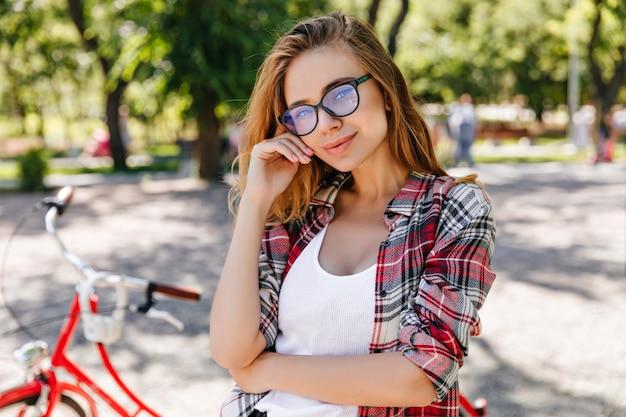 Adorable niña caucásica en vasos posando con placer en el parque. foto al aire libre de linda señorita en camisa a cuadros roja de pie junto a la bicicleta en la naturaleza.
