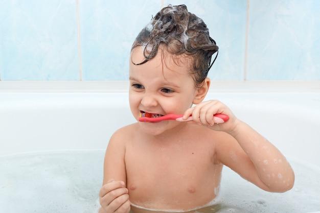 Adorable niña cepillándose los dientes, tomando un baño, jugando con burbujas de espuma.