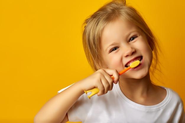Adorable niña cepillarse los dientes con cepillo de dientes para niños