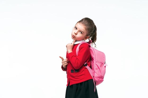 Adorable niña en chaqueta escolar roja, vestido negro, mochila señalando