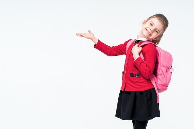 Adorable niña en la chaqueta roja de la escuela, vestido negro, mochila apuntando al espacio vacío mientras posa en el espacio en blanco. aislar