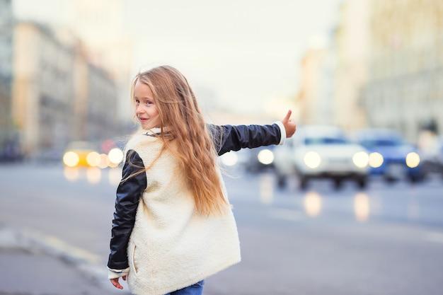 Adorable niña coger un taxi al aire libre en una ciudad europea
