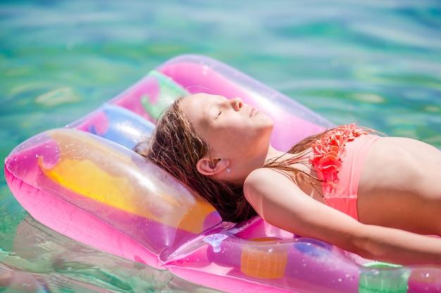 Adorable niña en colchón inflable en el mar