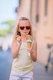 Adorable niña comiendo helado al aire libre en verano.