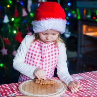 Adorable niña comiendo la masa para galletas de jengibre en la cocina