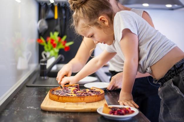 Adorable niña compartiendo pastel con madre