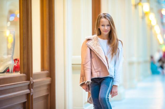 Adorable niña de compras en el centro comercial
