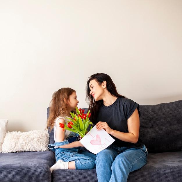 Adorable niña dando flores a su madre