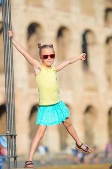 Adorable niña delante del coliseo en roma, italia. niño pasando la infancia en europa