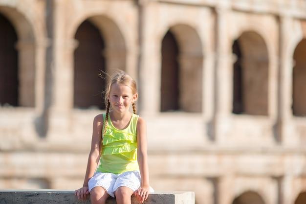 Adorable niña delante del coliseo en roma, italia. niño en vacaciones italianas