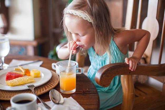 Adorable niña desayunando y bebiendo un cóctel de frutas
