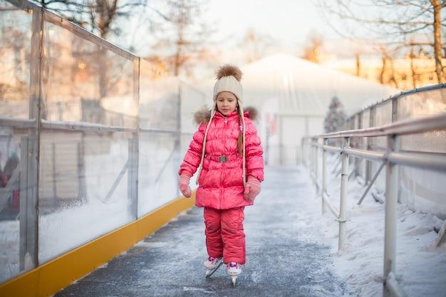 Adorable niña disfrutando de patinar en la pista de hielo