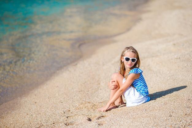 Adorable niña divertirse en la playa tropical durante las vacaciones