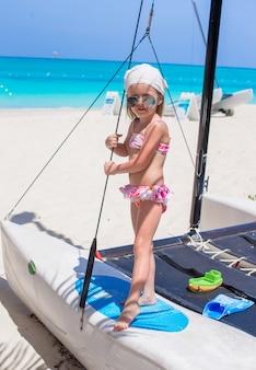 Adorable niña divertirse en un yate durante las vacaciones en el caribe