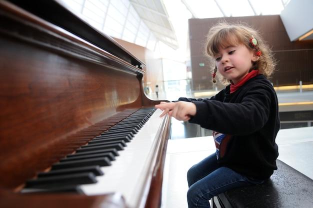 Adorable niña se divierte tocando el piano