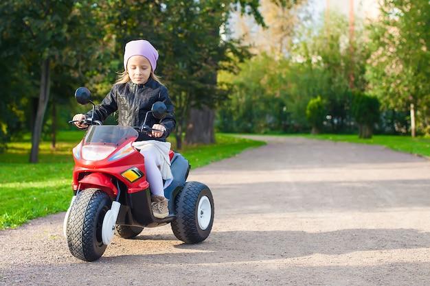 Adorable niña divirtiéndose en su motocicleta de juguete