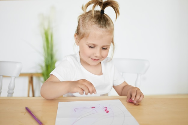 Adorable niña encantadora con cola de caballo sentada en el escritorio en el jardín de infantes frente a una sábana blanca, coloreando o haciendo figuras con plastilina o arcilla, con expresión facial feliz y alegre