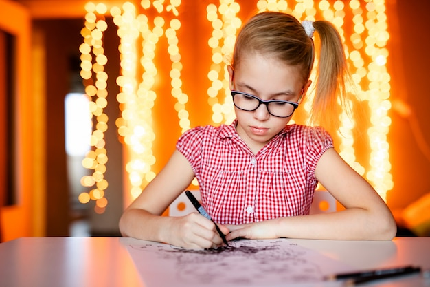 Adorable niña está escribiendo una carta a santa klaus sentada en la mesa