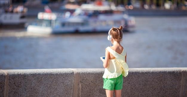 Adorable niña escuchando música en el parque
