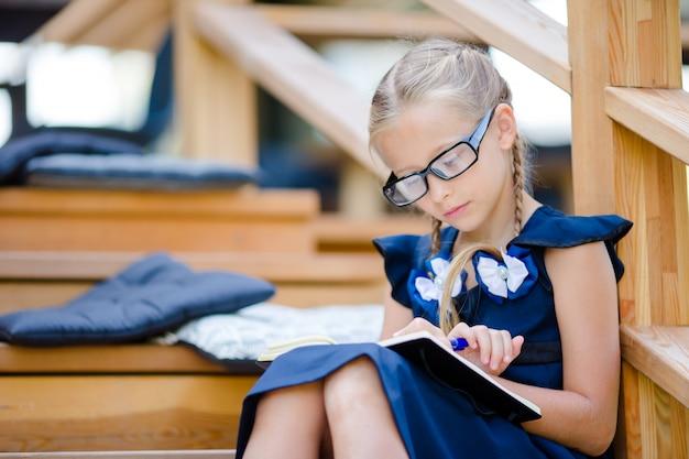 Adorable niña de la escuela con notas y lápices al aire libre. de vuelta a la escuela.