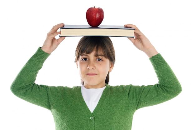 Adorable niña estudiando con libros y manzana en la cabeza