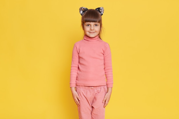 Adorable niña europea posando con orejas de gato aisladas en amarillo