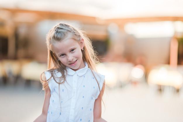 Adorable niña feliz al aire libre en la ciudad italiana.