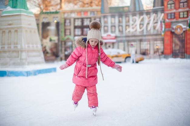 Adorable niña feliz disfrutando de patinar en la pista de hielo