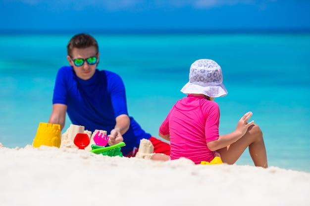Adorable niña y feliz padre jugando con juguetes de playa en vacaciones de verano