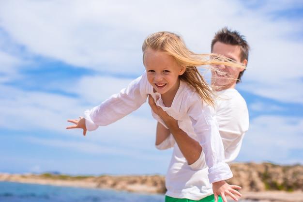 Adorable niña y feliz padre durante vacaciones en la playa