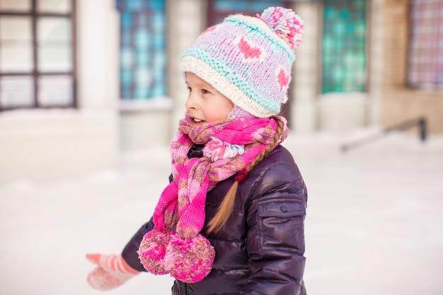Adorable niña feliz patinando en la pista de hielo