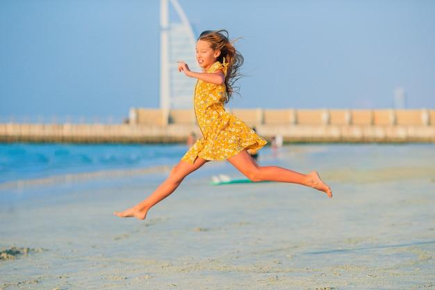 Adorable niña feliz en la playa blanca al atardecer