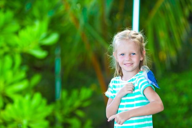 Adorable niña feliz en la playa con pajarito colorido