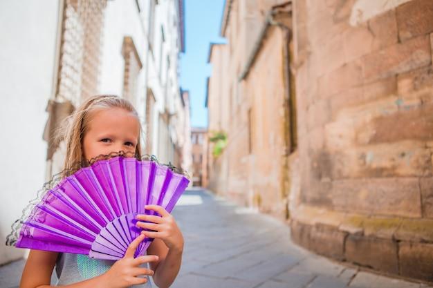 Adorable niña feliz tomando selfie al aire libre en la ciudad europea. retrato de niño caucásico disfrutar de las vacaciones de verano en la ciudad vieja